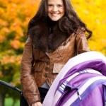 Happy mother with pram — Stock Photo