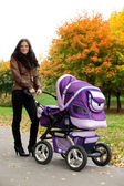 Happy mom with pram — Stock Photo