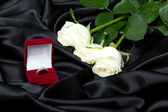 Wedding concept white roses and ring in red box — Stock Photo