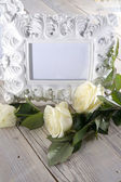 Blank photo frame and white roses — Stock Photo