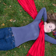 Brunette beautiful woman is in red scarf lying on the grass. — Stock Photo