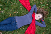 Brunette beautiful woman is in red scarf lying on the grass. — Foto de Stock