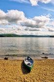 Green canoe on lake shore — ストック写真