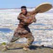 Chukchi man dancing a folk dance against spring landscape — Stock Photo