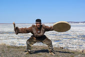 Chukchi man dancing a folk dance against spring landscape — Stock Photo
