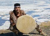 Chukchi man sitting against against spring landscape — Stock Photo