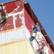 Stock Photo: Steeplejacks painting the house against the blue sky