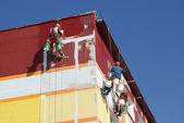 Steeplejacks painting the house against the blue sky — Stock Photo