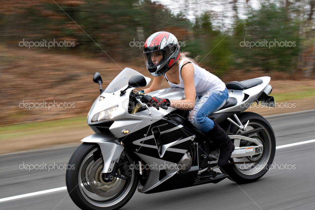 A woman drives a motorcycle at highway speeds with motion blur visible in the background. — Stock Photo #7361960
