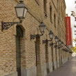 Streetlights and brick facade, History Museum of Catalonia, Spain — Stock Photo #7231599