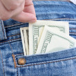 Jeans with a woman's hand and money in pocket — Stock Photo