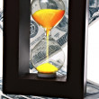 Sand clock with gold sand on dollar background — Stock Photo #6778909