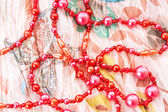 Red chaplet on textile background — Stock Photo