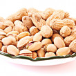 Few peanuts and dish isolated on white - Stock Photo