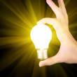 Royalty-Free Stock Photo: Bright yellow incandescent bulb in hand isolated on black backgr