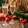 Two glasses with champagne and New Year decorations — Stock Photo