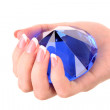 Giant blue diamond in hand isolated on white — Stock Photo