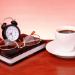 Cup of coffee, book, clock and calculator on wooden table — Stock Photo #6783921