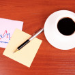 Royalty-Free Stock Photo: Cup of coffee, a couple of stickers, chart and pen on table back