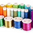 Stock Photo: Semicircle of many-coloured bobbins of thread isolated on white
