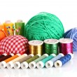 Coloured bobbins of threads, woolen balls and cushion for pins - Stock Photo