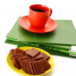 Chocolate cookie and cup of coffee on magazines isolated on whit — Stock Photo #6784494