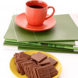 Chocolate cookie and cup of coffee on magazines isolated on whit — Stock Photo #6784498