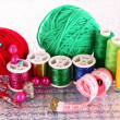 Coloured bobbins of threads, woolen balls and cushion for pins i - Stock Photo