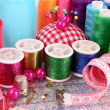 Coloured bobbins of threads, woolen balls and cushion for pins i — Stock Photo