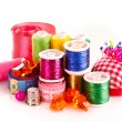 Stock Photo: Coloured bobbins of threads, woolen balls and cushion for pins