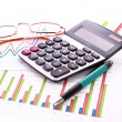 Coins, pen, calculator and charts — Stock Photo