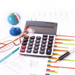 Calculator, pen, glasses, globe and some charts - Stock Photo