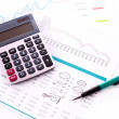 Calculator and some financial charts - Stock Photo