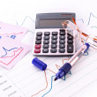 Stock Photo: Calculator and some financial charts