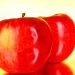 Two red apples on red background — Stock Photo