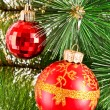Red Christmas balls among green new year tree — Stock Photo #6786833