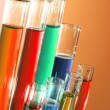 Test tubes on orange background - Foto Stock
