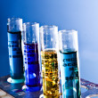Test tubes on blue background - Stok fotoğraf