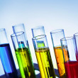 Multicoloured test tubes in the stand on blue background - Foto Stock