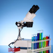 Laboratory metal microscope and test tubes with liquid on blue b — Stock Photo #6788717