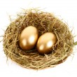 Three golden hen's eggs in the grassy nest isolated on white — Stock Photo #6788842