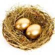 Three golden hen's eggs in the grassy nest isolated on white — Stock Photo #6788844