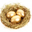 Foto de Stock  : Three golden hen's eggs in the grassy nest isolated on white