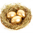 Foto Stock: Three golden hen's eggs in the grassy nest isolated on white