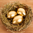 Three golden hen's eggs in the grassy nest on the wooden table — Stok fotoğraf