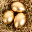 Royalty-Free Stock Photo: Three golden hen\'s eggs in the grassy nest on the wooden table