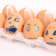 Group of brown hen's eggs with different faces in the box — Stock Photo