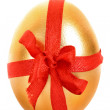 One golden hen's egg with a red ribbon isolated on white - Foto Stock