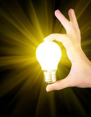 Bright yellow incandescent bulb in hand isolated on black backgr — Stock Photo