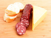 Sausage, bread and cheese on wooden plate — Stock Photo